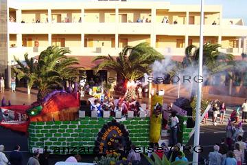 Prunkwagen in Form einer Burg, mit Drachenkopf und den Telnehmern des Karneval auf der Insel Lanzarote besetzt. Los Guerreros del Dragon, kann man als Aufschrift auf dem Wagen für den Karnevalsumzug erkennen.