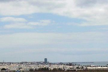 Arrecife, Hauptstadt von Lanzarote. Im Hintergrund hebt sich das Hochhaus von Arrecife neben den kleineren anderen Häusern deutlich ab. Das Bild ist von Süden in Richtung Arrecife fotografiert. Sozusagen vom Flughafen.