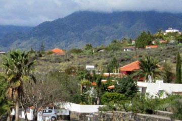 Fincas auf La Palma auf lanzarote-reise.org zu sehen - im Vordergrund erkennt man das schön, die Zufahrt zur Finca und den Mietwagen hinter der Toreinfahrt, die Satellitenschüssel an den rote Dachziegeln, den schön angelegten Garten und im Hintergrund weitere spanische Fincas der kanarischen Inseln, so sieht das aus.