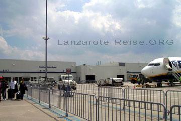 Passagiere auf dem Gate zum Flugzeug hin mit ihrem Handgepäck laufend das bereits auf dem Rollfeld zum einsteigen bereit steht, beim Lanzarote Urlaub auf den Kanarischen Inseln die zu Spanien gehören und vor Nordafrika und Marokko liegen.