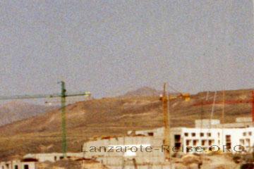 Baukräne und eine im Bau befindliche Hotelanlage auf der kanarischen Insel Lanzarote mit nur vier Stockwerken.