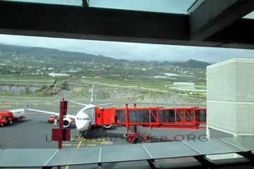 La Palma Flieger vor dem Terminal zur Abfertigung und Betankung und dem roten Gateway als Flugsteig mit dem Aeropuerto verbunden über den die Passagiere in das Flugzeug zum La Palma Flug auf die kanarischen Inseln - Spanien einsteigen.