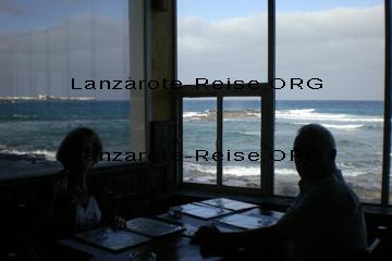 Hier auf dem Bild, das ist zwar die Küste von Lanzarote aber mit einem felsigen Strand. Das Bild zeigt  Mama und Papa in einem Fisch-Restaurant, wo man beim Essen durch die Fensterscheibe direkt aufs Meer schauen kann.