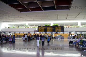 Passagiere im Flughafen und der Abflughalle auf der Kanarischen Insel Lanzarote die auf Ihren Flug warten oder am Ticket-Schalter ein checken.