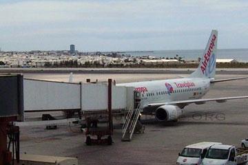 Ein Flugzeug angedockt an der Gangway auf dem Flughafen auf der Kanarischen Insel Lanzarote und im Hintergrund die Inselhauptstadt Lanzarote und gut zu erkennen das Hochhaus am Strand in etwa 5 Kilometer Entfernung.