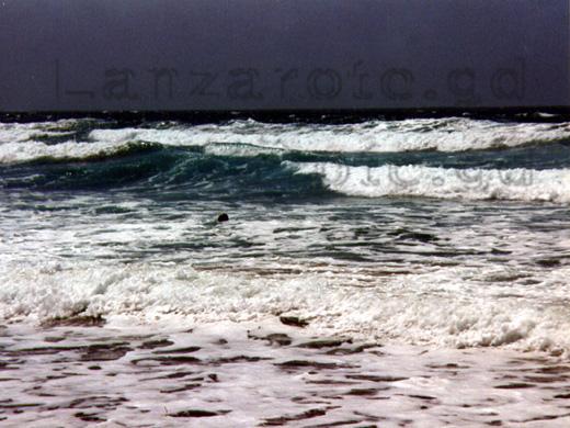 Schwimmer im Atlantik in der Bucht von Famara auf der Kanarischen Insel Lanzarote.