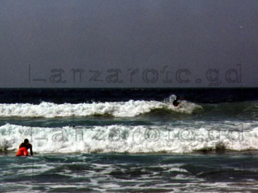 Wellenreiter liegt auf seinem Surfbrett in den Wellen der Bucht von Famara um weiter hinaus aufs Meer zu paddeln.