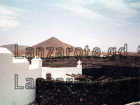 Ein weiß angemaltes Ferienhaus in Yaiza auf Lanzarote zwischen erkalteter Lava.
