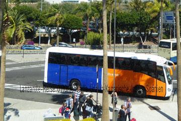 Touristen bei der Weiterreise die gerade in einen Reisebus einsteigen wollen nachdem das Reisegepäck verstaut wird zeigt dieses Bild vom Flughafen Teneriffa-Süd auf der Kanarischen Insel vor dem Terminal.