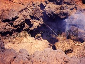 Feuershow Vorführung mit Reisig, Timanfaya Feuerberge, kanarische Insel Lanzarote, zuerst nur leichter Rauch zu sehen.